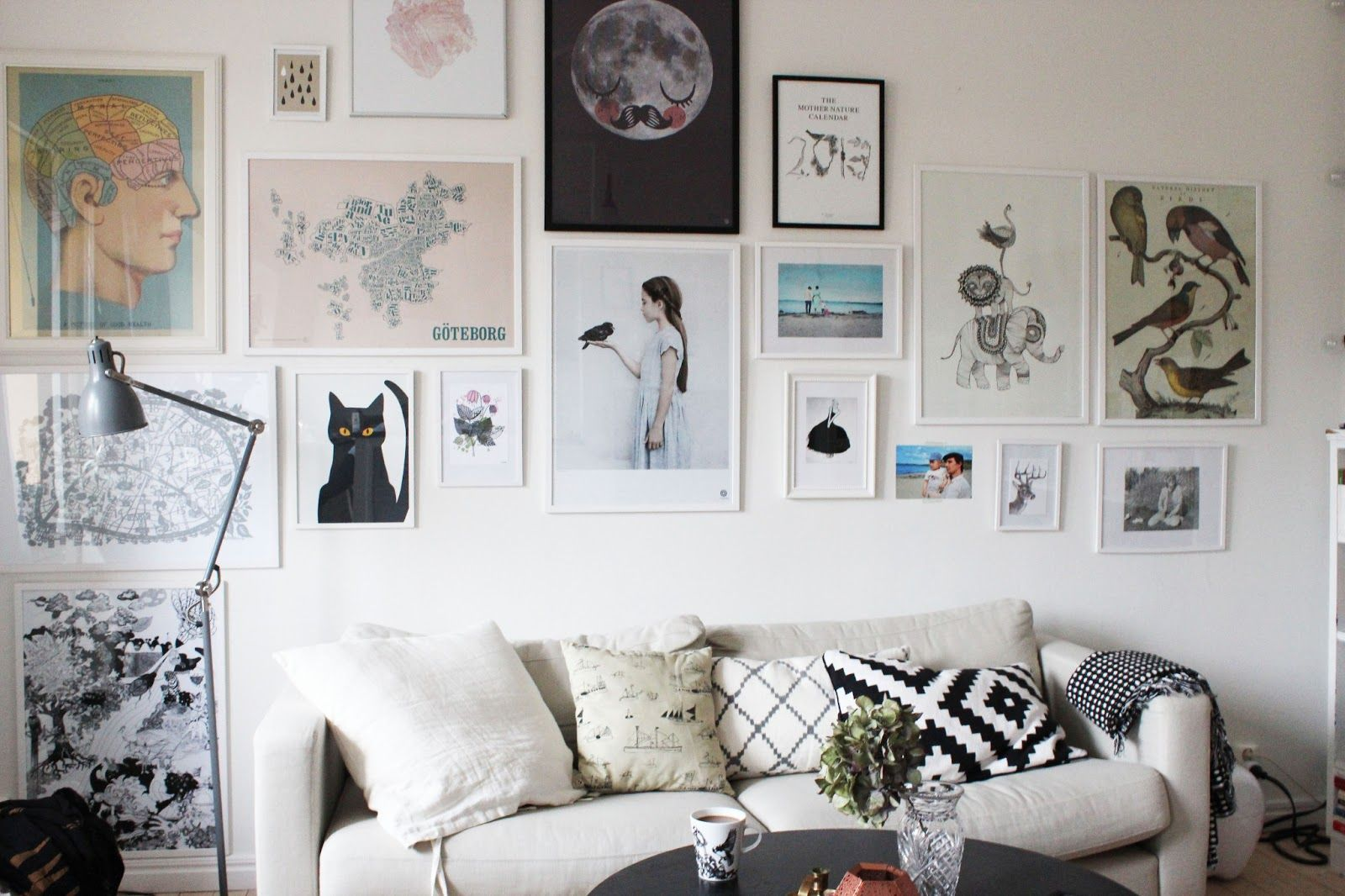 Great picture collection above monochrome sofa and cushions.
