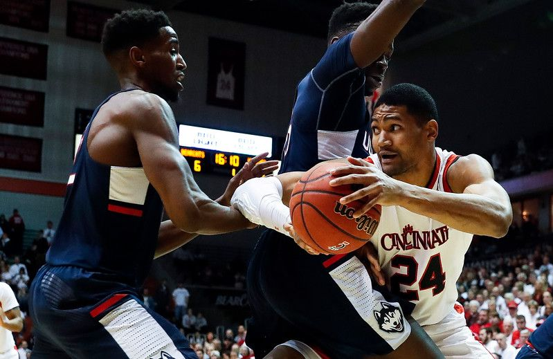 Cincinnati's Kyle Washington (24) looks to pass around Connecticut's Amida Brimah, center, and Kentan Facey, left, in the first half of an NCAA college basketball game, Saturday, Feb. 4, 2017, in Cincinnati. (AP Photo/John Minchillo)