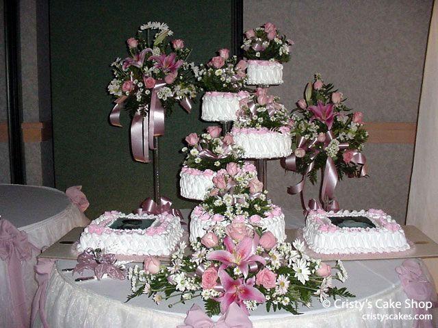 El pastel es blanco y rosado.  El pastel tiene muchos flores rosados.