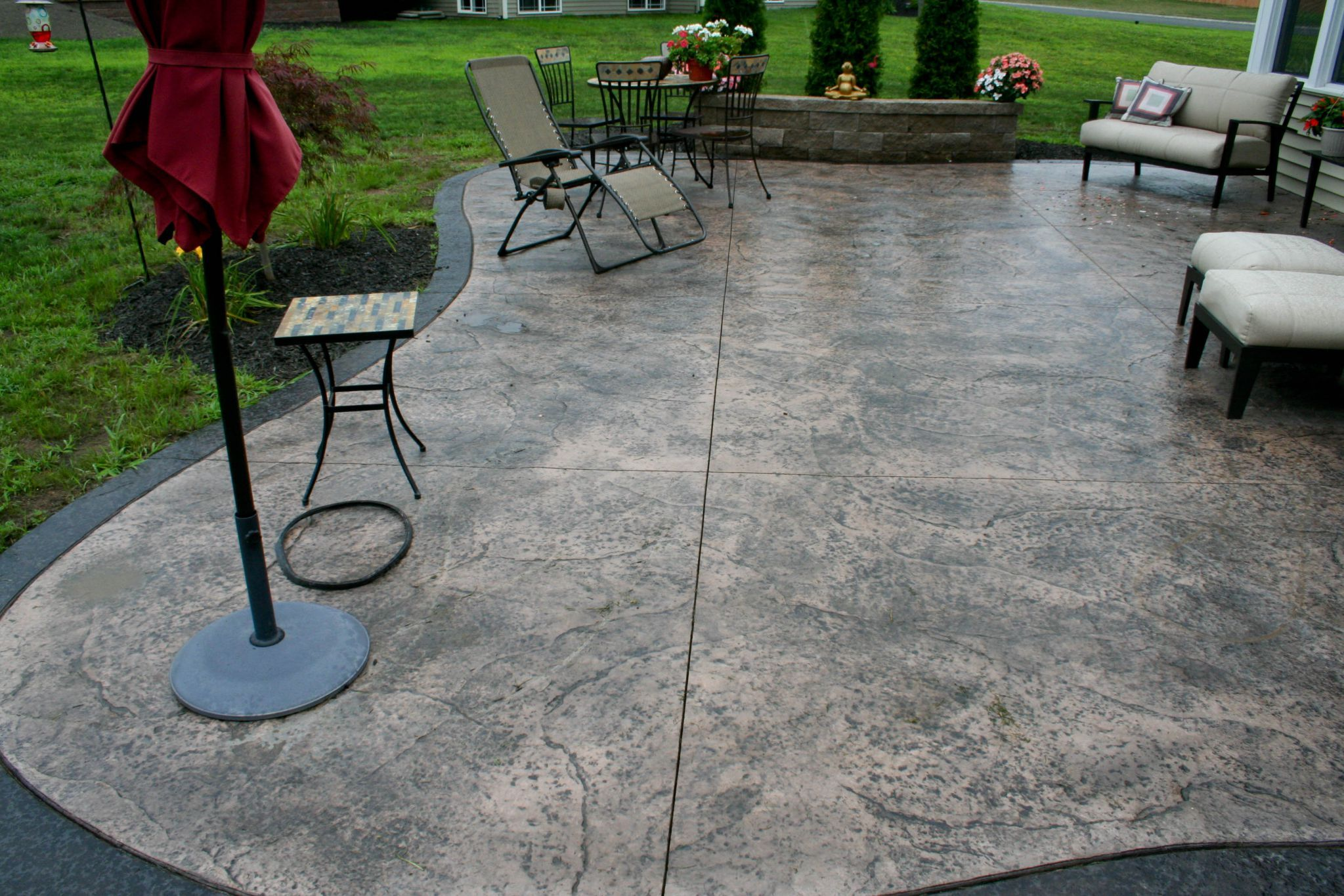 Comfortable lounge chair and cozy ottomans on stamped concrete patio with unique flooring