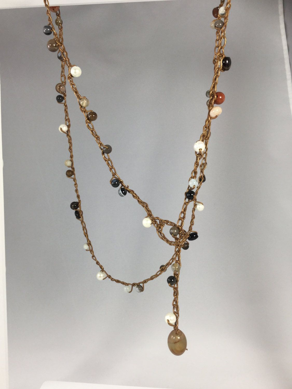 """This gemstone necklace/bracelet has been crocheted with beautiful black agate, red and white agate, spotted sodalite, brown goldstone and sea opal glass, White fresh water pearl potato beads, gold leather cord with crocheted loop and agate bead. Black agate, red and white agate, spotted sodalite, brown goldstone, sea opal glass, bead closure • 23"""" can be wrapped 2x,"""