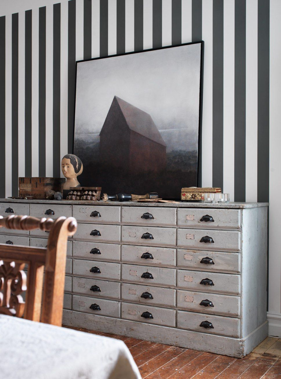 When you have a busy wall, like the striped one pictured here, you need to keep the custom framed art simple. This large, minimally framed photograph adds just the dimension and interest this wall needed, without competing with the wallpaper.