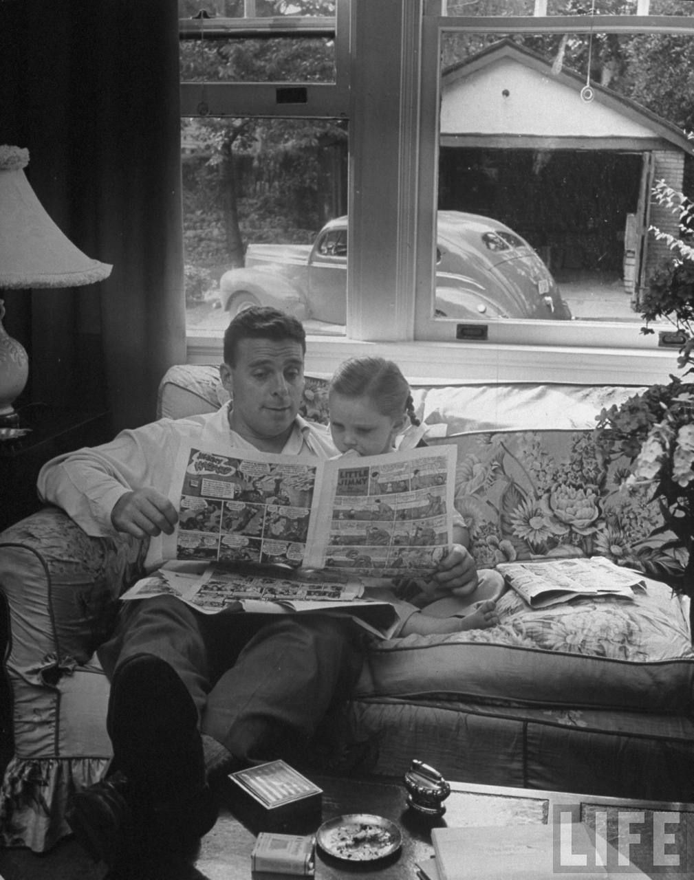 Father reading the Sunday comic pages to his daughter, 1946. (Nina Leen)