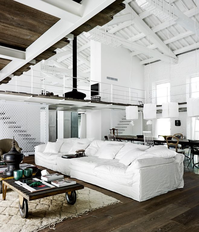 Italian designer Paola Navone remodeled a 19th-century factory in Spello, Italy, to serve as a family home. She added reclaimed wood floors and whitewashed the building's original structure to turn one double height room into a spacious two-story apartment.  Photo by Wichmann + Bendtsen.