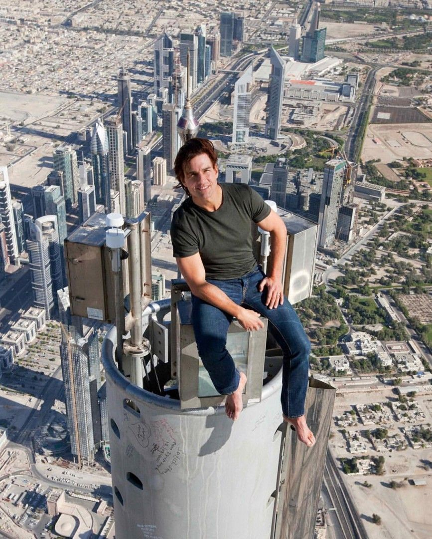 Tom Cruise sentado no topo do Burj Khalifa, em Dubai, durante as ...