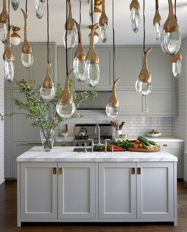 Brass Kitchen Lights: Exquisite gray kitchen features gray shaker cabinets adorned with antique  brass inset pulls paired with white,Lighting