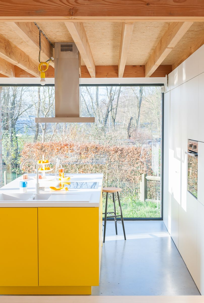 bright yellow kitchen island, floor to ceiling windows ...