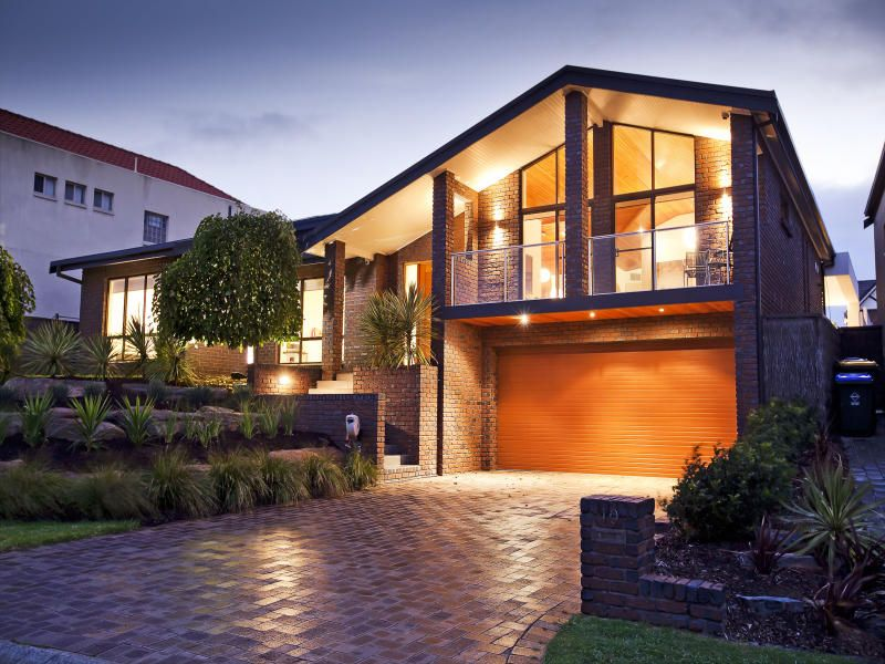 brick modern house exterior with bay windows & decorative lighting
