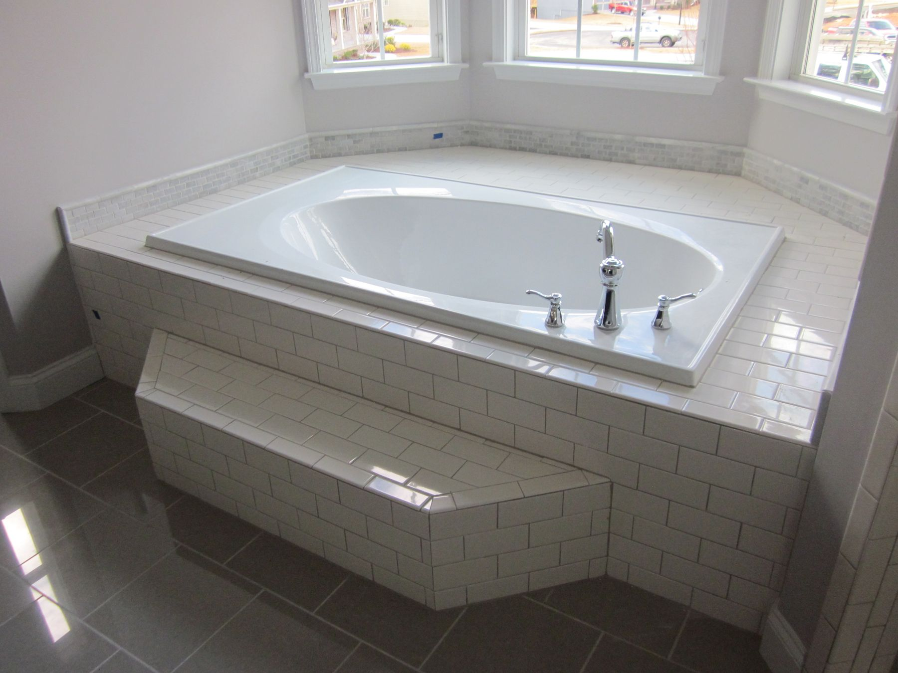 The master tub with white subway tile surround gray for Tub master