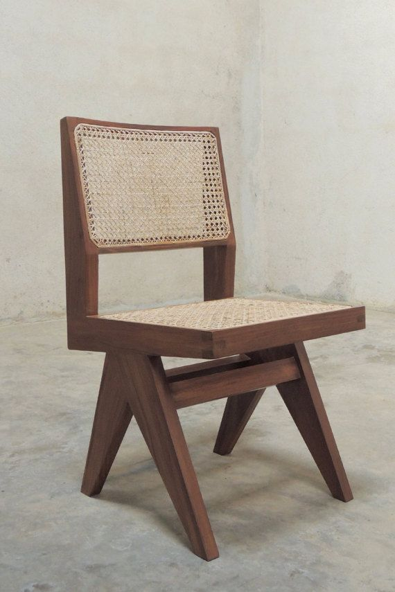 An Armless Chair Based On A Design Created By Pierre Jeanneret