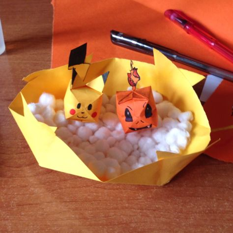 Photo of Pokémon origami Pikachu and Charmander in a box of cotton balls. Easy origami D…