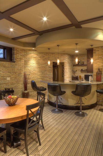 Very cool basement design. A curved counter, a circular soffit and pendant  lighting define