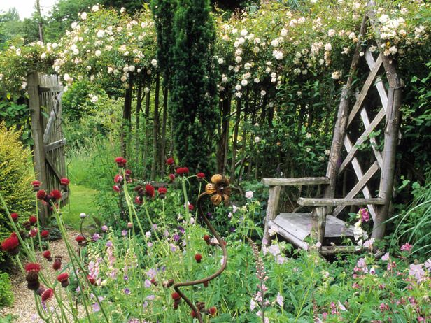 An Old Rustic Seat, Surrounded By Soft Drifts Of Pink Perennials And A  Delicate White