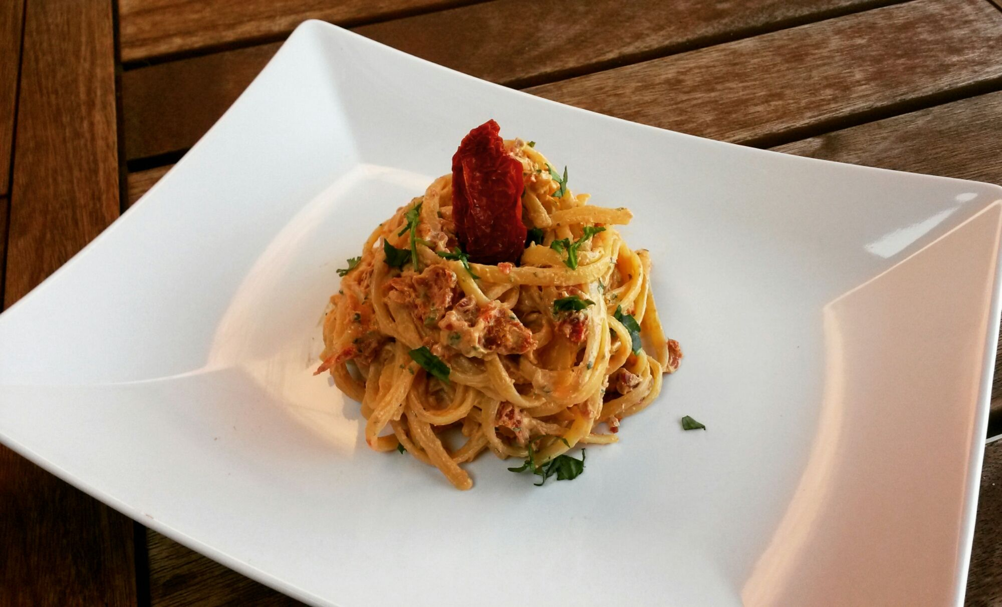 Spaghetti con pesto di ricotta, pomodori secchi e rucola.
