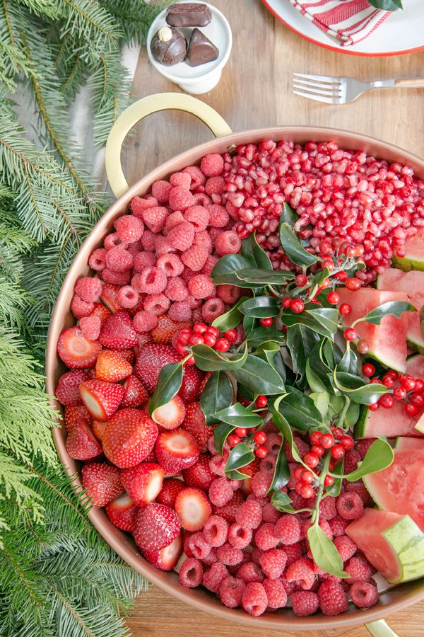 Plan a festive feast by decking the table with classic colors and holiday-themed tokens, from green garlands to red winter berries.