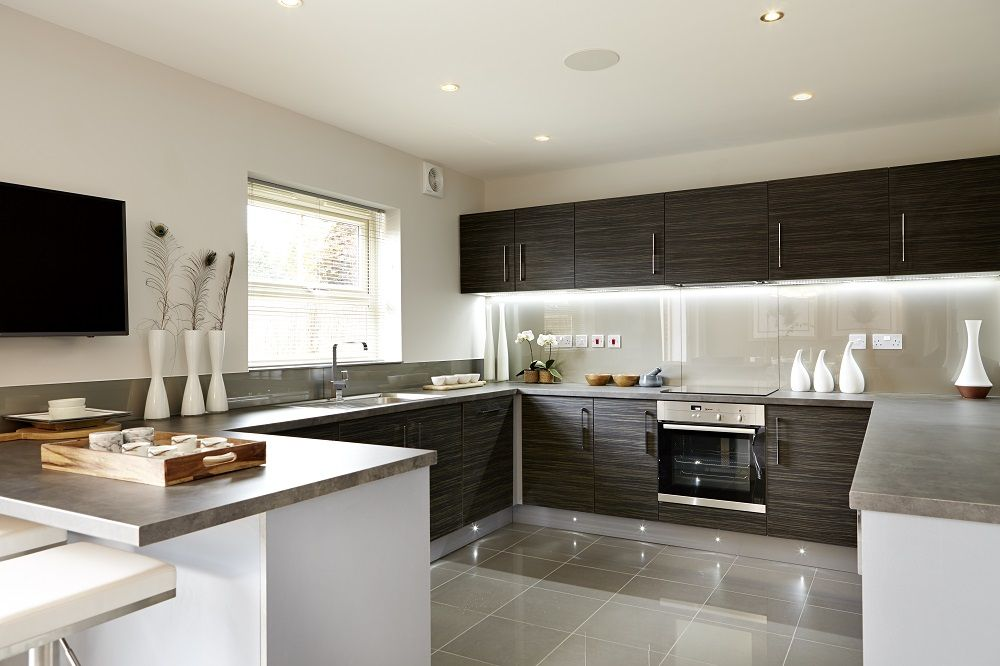 The open plan kitchen and dining room is divided by a breakfast bar  French doors lead onto the garden in four bed Montreux Strata Kitchen