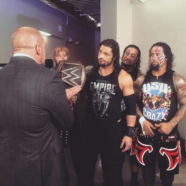 Roman Reigns handing the WWE World Heavyweight Title back to The Authority.