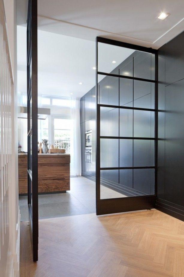 Stalen deur met overgang hout naar betonvloer. Mooie overhang en handige vloer in de keuken