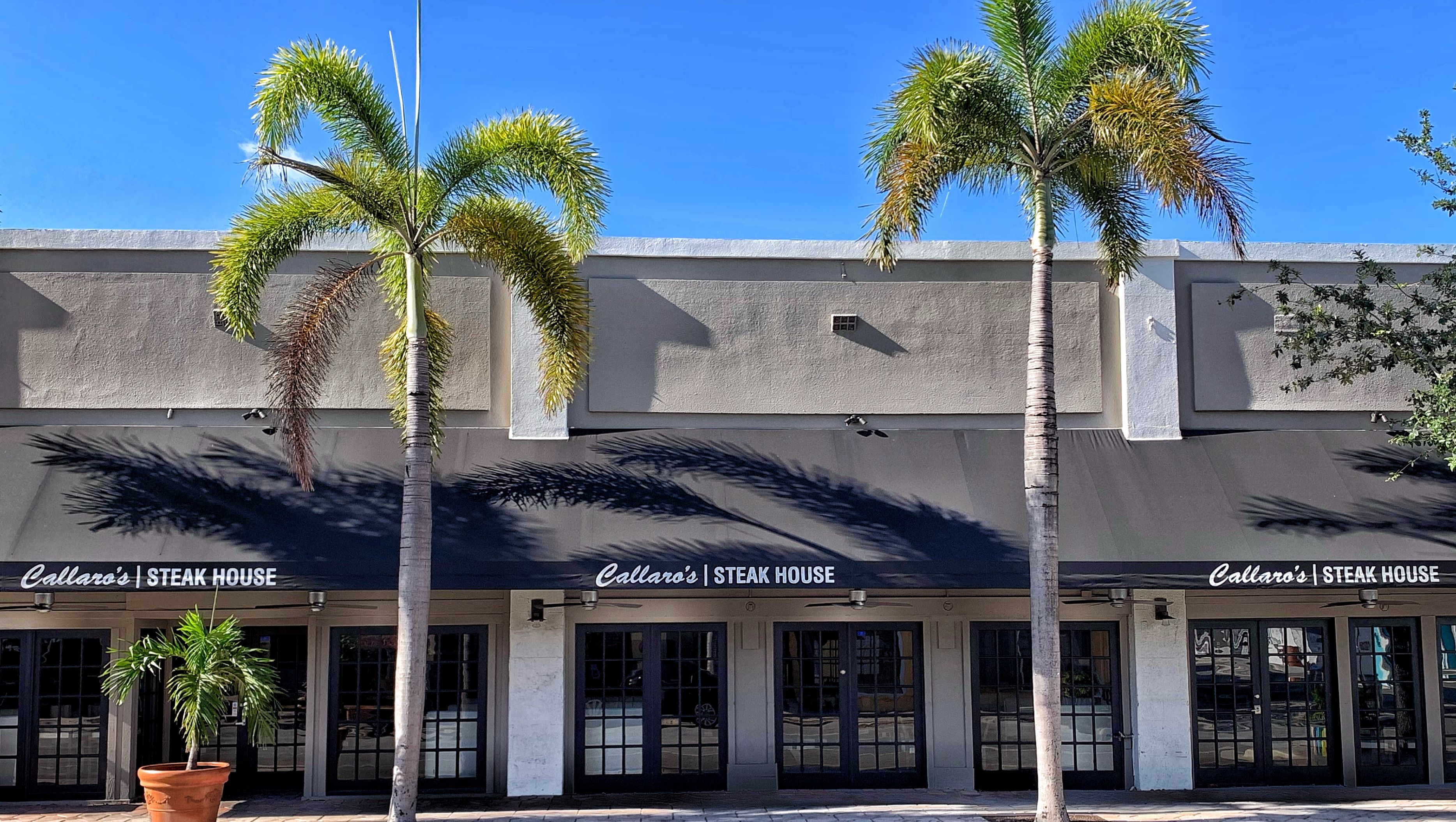 Custom black awnings on the front of Callaros Steak House in downtown Lake Worth Beach. This classic style of awning allows for tables for patrons to eat outside, while being protected from the sun on hot Florida summer days or from the afternoon rainstorms. The front panel allows for custom and consistent branding #southflorida #palmbeach #lakeworthbeach #awning #steakhouse #restaurants