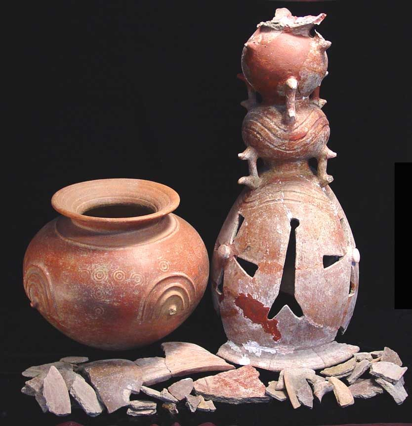 AN IMPORTANT LARGE ETRUSCAN IMPASTO HOLMOS AND DINOS, Circa 7th Century B.C. The holmos was one of the utensils required for a banquet. The stand, which is hollow inside, once supported the accompanying dinos, or large cauldron. The holmos' structure consists of three elements fired together as a single piece. It is decorated with openwork rosettes with knobs at their centers, cutout lines between. It sits on a flaring base and is topped by an upper conical portion.