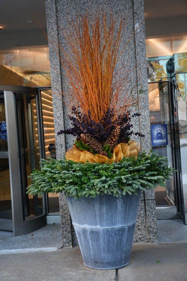 Winter urn arrangement - cut twigs, fresh cut greens, dyed kiwi vine, sugar pine cones, gold sinamay, fresh cut magnolia.