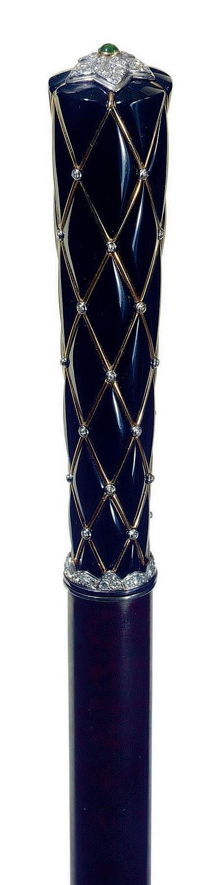 A FRENCH DIAMOND-MOUNTED BLACK ENAMEL METAMORPHIC CANE <br />POSSIBLY BY CARTIER, CIRCA 1920 <br />The quilted enameled handle inset with yellow gold stringing punctuated with diamonds below a green stone and pavé diamond rosette rising to reveal a miniature clock with later quartz movement, mahogany shaft<br />36½ in. (93 cm.) high <br />