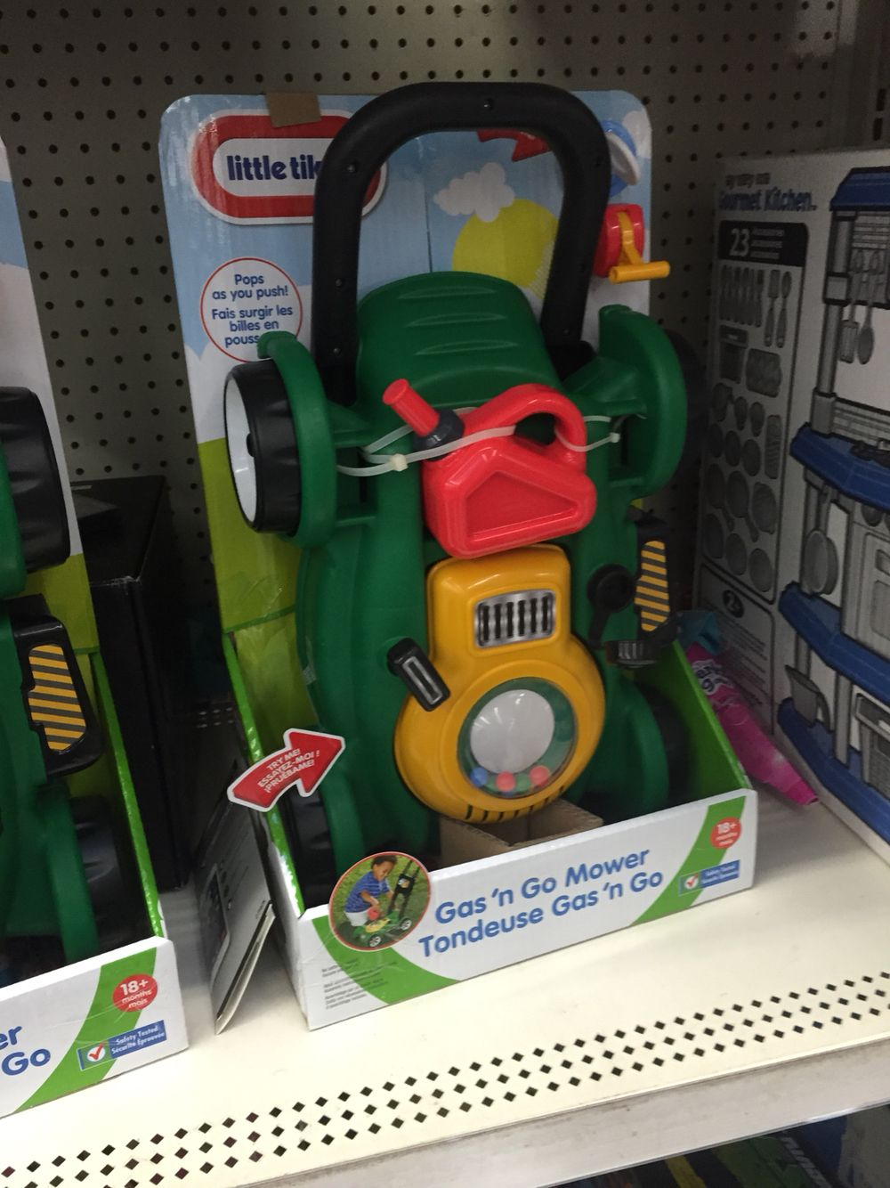 Toy lawn mower at Walmart near the electronics on the back
