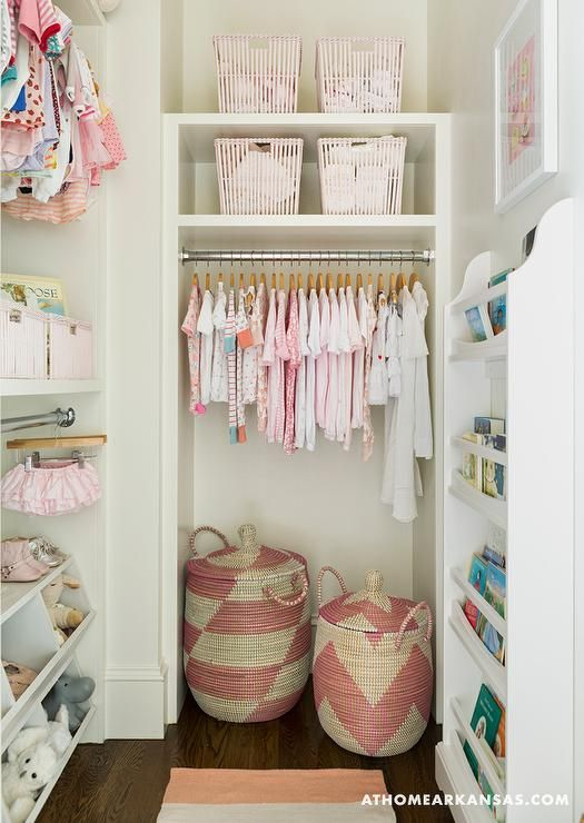 Melissa Haynes - Chic nursery closet with pink accents features shelves lined with pink bins placed over a nook fitted with a clothes rail and pink woven baskets.