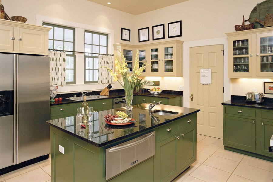 Well-Seasoned Style - 110 Beautiful Kitchens - Southernliving. These homeowners made clever paint choices. By selecting a dark green for the base cabinetry and island, they grounded the space with an appropriate connection to nature. Pale gold upper cabinets bring a welcomed lightness to the scheme. Interestingly, the units with glass-panel doors reveal that the same shade of green is used within.