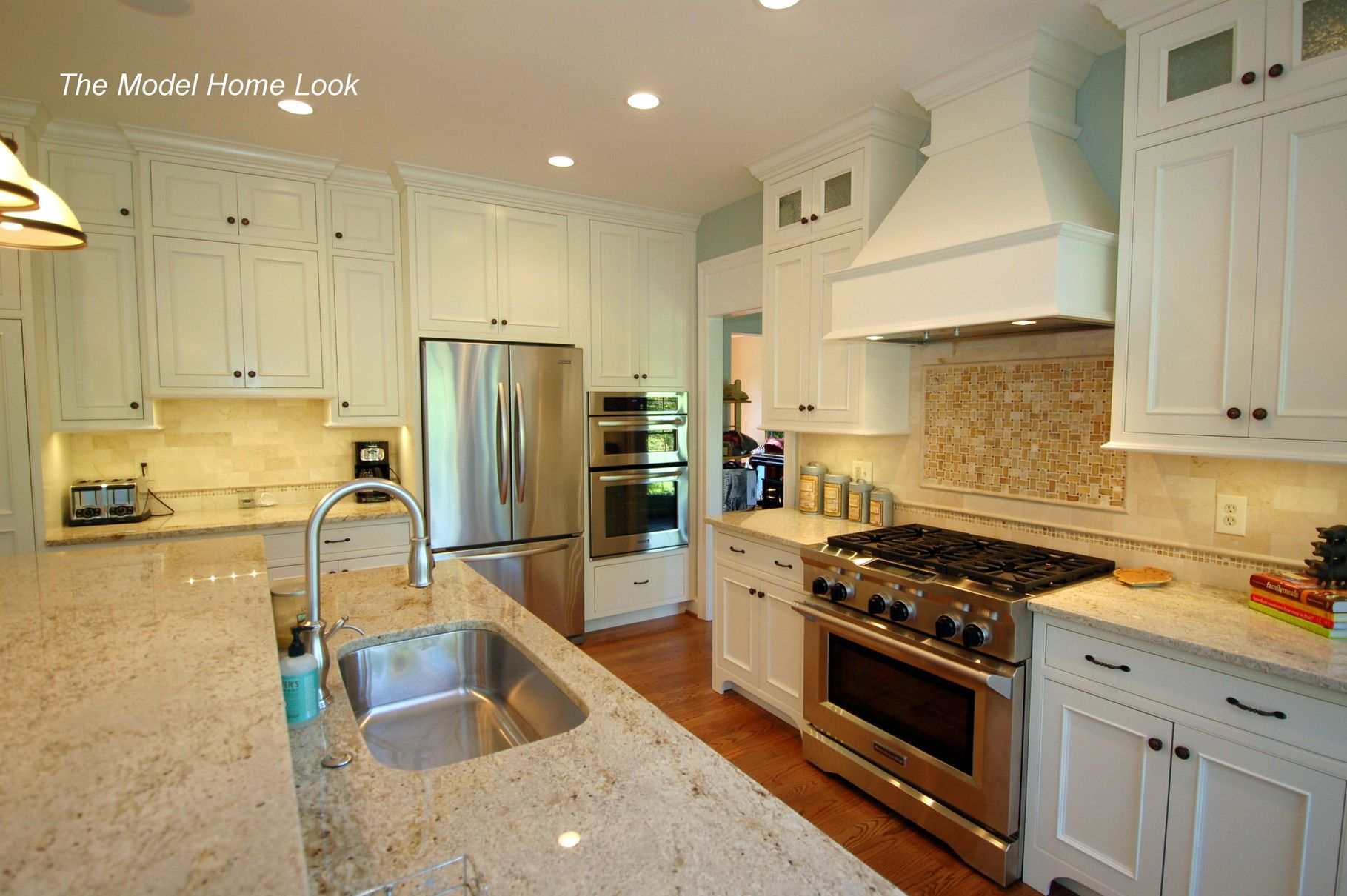 granite counter top, hardwood floors, painted cabinets with beaded