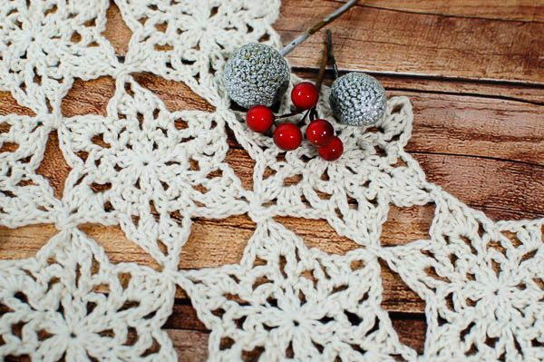 Add some winter whimsy to your table with this pretty Snowflake Table Runner Crochet Pattern ... it's the perfect accent for the holiday season and throughout the winter months! #crochet #fiber