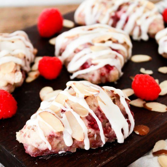 Scones filled with thin slices of almonds, fresh raspberries, mini pockets of butter, & perfectly sweetened with a drizzle of icing.