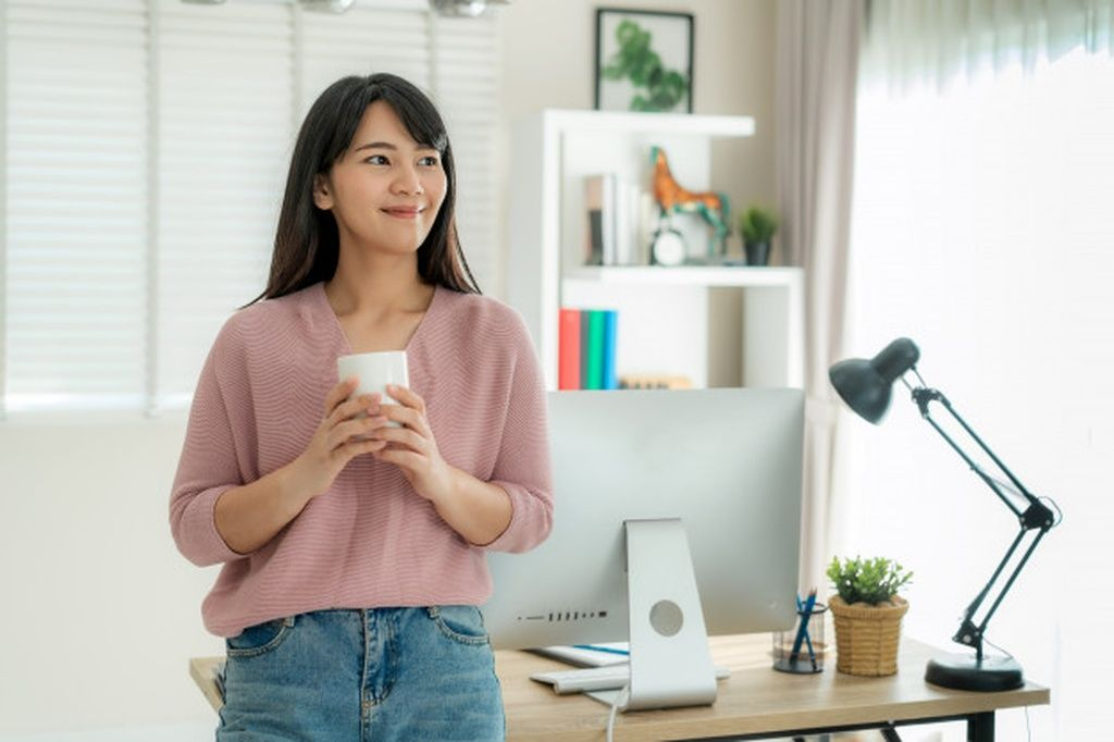Asian beautiful young woman work from home working on computer and drinking  coffee while relax from her work standing in living …   Design, Asian,  Working from home