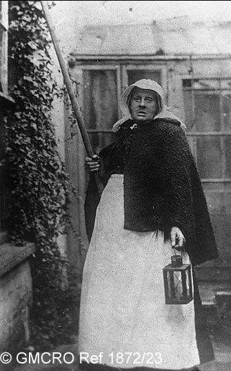 """Grannie Cousins"""", the local 'Knocker up' in c.1912. (GB124.DPA/1872/23).  Standing behind the studio and beside the dining room window of 12, North Street, holding her pole up to a bedroom window. Harrie Belben sold copies of this postcard to visitors to Poole as a curiosity and he and Grannie Cousins shared the proceeds."""