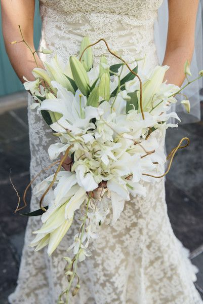 <strong class='info-row'>G.Chapin Studios</strong> <div class='info-row description'>The bride's bouquet featured lilies, dendrobium orchids, and curly willows.     Venue/Caterer: Galvez Restaurant     Event Planner: Weddings by Lulu    Dress Designer: Modern Trousseau from Wedding Belles     Floral Designer: Erin Steen, Florist</div>