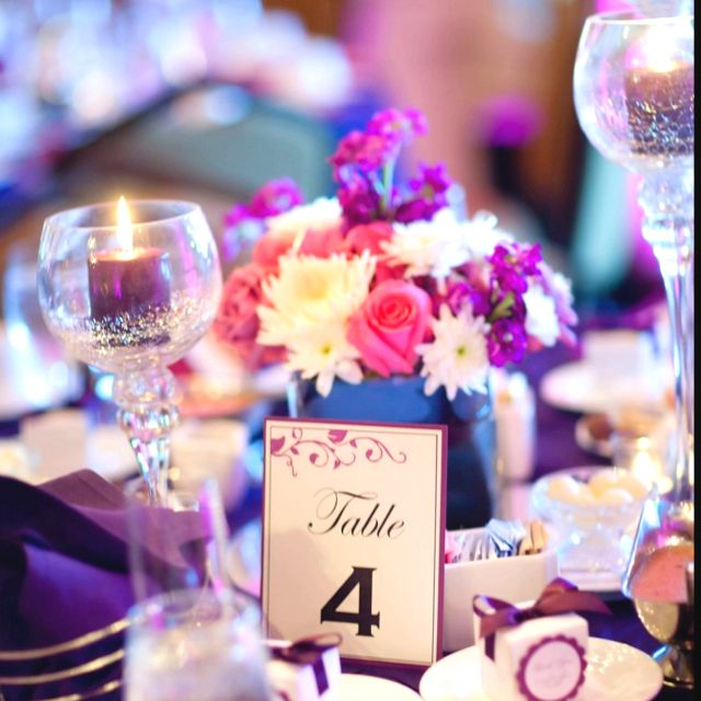 centerpiece with table number, candles and pink flowers