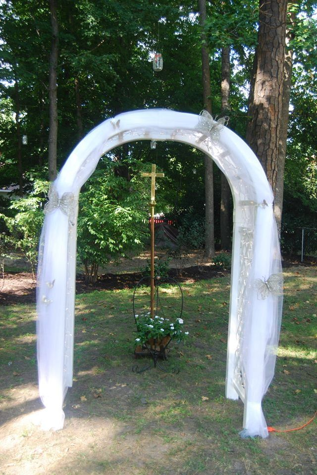 Rustic Outdoor Wedding Arch Is Covered With Christmas Lights And Tulle Butterflies