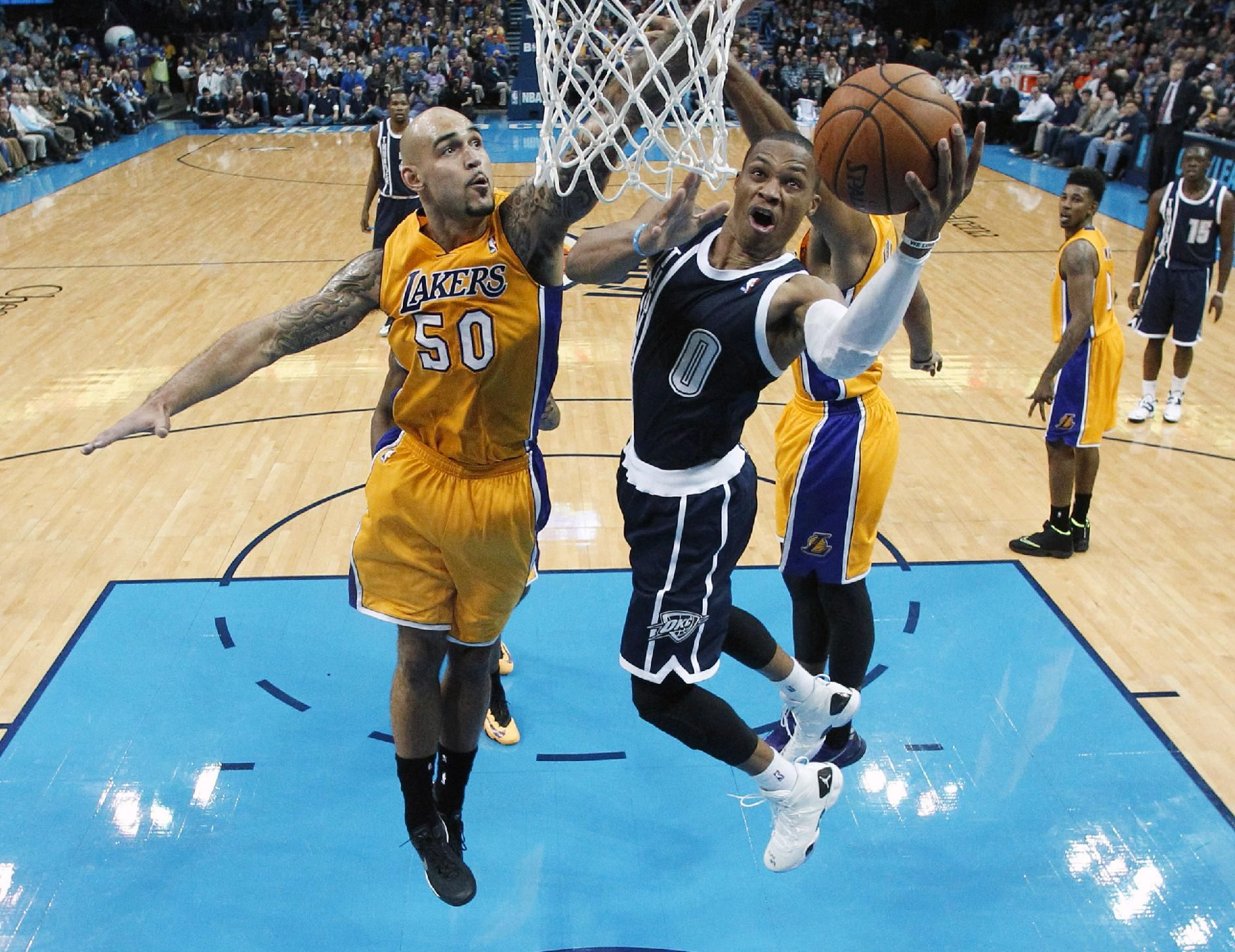 Oklahoma City Thunder guard Russell Westbrook (0) shoots in front of Los Angeles Lakers Robert Sacre (50) in the second quarter of an NBA basketball game in Oklahoma City, Friday, Dec. 13, 2013. Oklahoma City won 122-97. (AP Photo/Sue Ogrocki)
