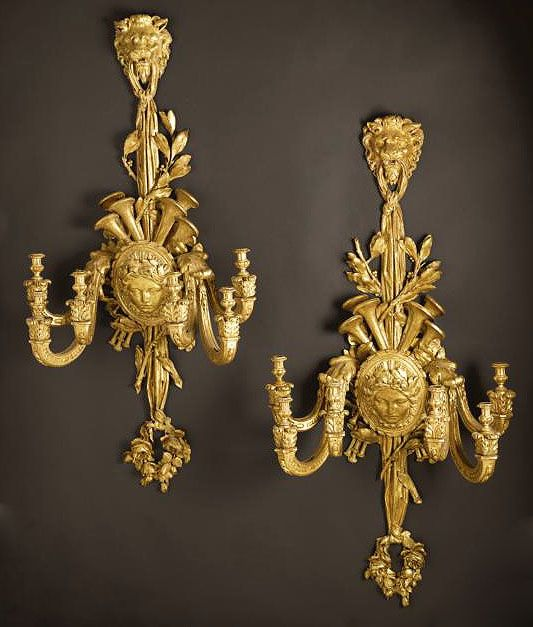 An Important and Palatial Pair of French 19th Century Louis XV Style Gildwood Carved Six Light Wall Appliques (Sconces), the six scrolled candle-arms emanating from a center medallion with a female mask and surmounted with musical instruments, acanthus and leaves, the top with a carved lion head holding a draped swaged tassel supporting the entire fixture. Circa: Paris, 1870