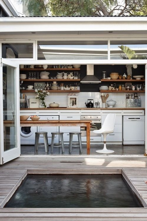 Indoor outdoor living space. Kitchen with table and sliding glass doors onto deck.