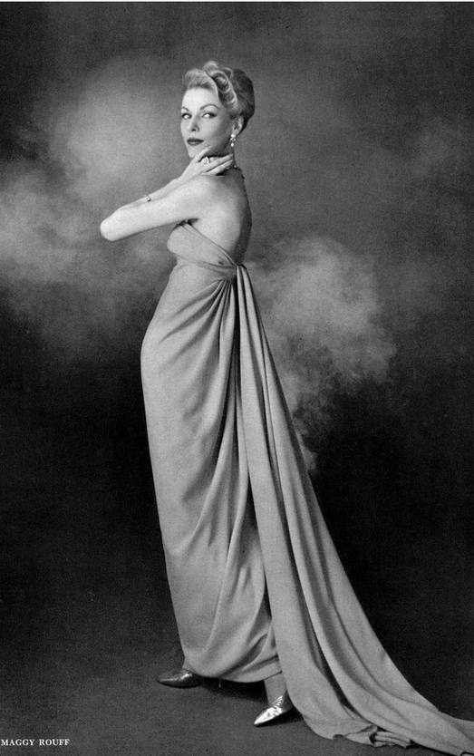 1958 Dorothy in draped crêpe evening gown, panels tied in the back, falling to the floor in train, by Maggy Rouff,