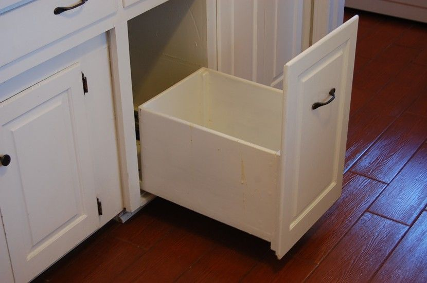 Furniture Delectable White Kitchen Cabinet With Trash Can Slide Out And Wooden Door Also Brown Laminated Floor As Well