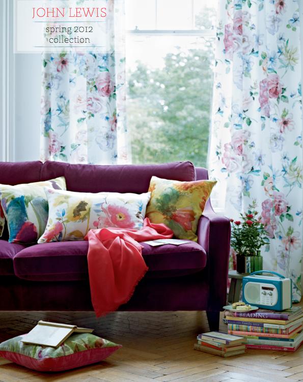 Ambiente bem feminino com sofá roxo, cortina e almofadas florais