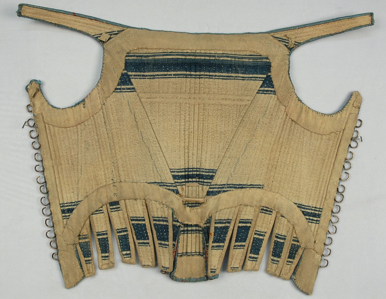 LOT 496 SILK CORSET and STOMACHER, AMERICAN or EUROPEAN, 18th C. Blue faille with polychrome floral brocade, the corset having straps, white leather tabs and silver metal hooks, blue and white striped lining with leather facings, B-29, W-22, center front L-14. Stomacher TRIMMED in metallic gold passementerie, padded and backed in printed cotton, 15 x 12. (Edge wear, leather soiled, metallic loss, few holes to stomacher) overall very good. MMA. $1,800