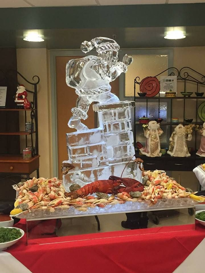 Ice sculpture of Santa going down the chimney with presents as a centerpiece to a food display. #icesculptures #icesculpturestampa #holidayice