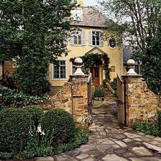 French cottage by M.A.M.  Classic French country cottage, beautiful stone entry gate