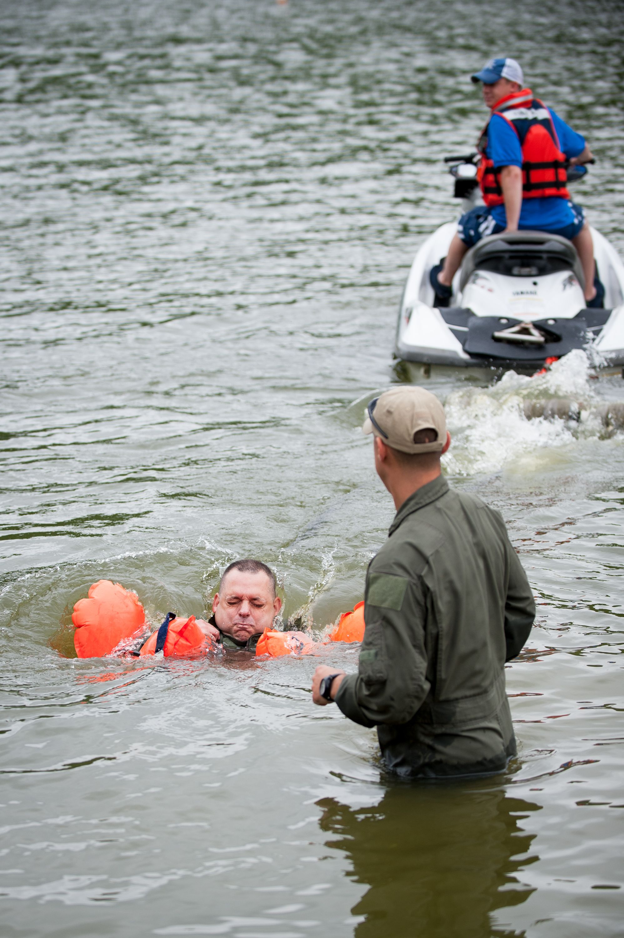 Maj. Todd Franks, a pilot in the Kentucky Air National Guard's 165th Airlift Squadron, is pulled across Taylorsville Lake in Taylorsville, Ky., by a personal watercraft June 5, 2014, as part of routine survival training. The exercise is designed to simulate what could happen to aircrew members who've parachuted into water when the wind catches their open chutes and drags them across the surface, posing the risk of drowning. (U.S. Air National Guard photo by Maj. Dale Greer)