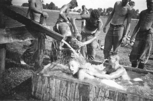 Young Wehrmacht soldiers making good use of a cattle trough for their morning ablutions