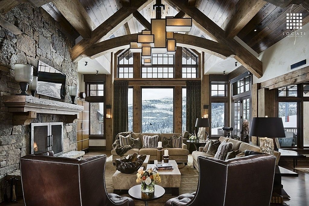 An Elegant Living Room Featuring A Large Stone Fireplace Natural Wood Cathedral Ceiling