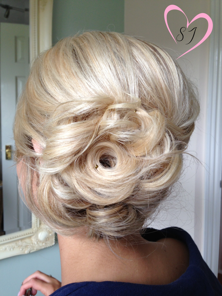 blonde hair curled pinned updo done for a wedding guest